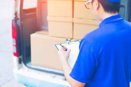 Концепция доставки - мужчина-курьер почтовой доставки перед грузовым фургоном, перевозящий упаковку с коробкой для осмотра и обслуживания