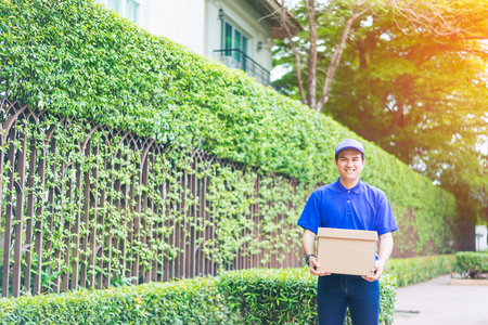 Delivery concept - Smiling happy young asian handsome male in front of house delivering package carrying box with service mind and blue uniform