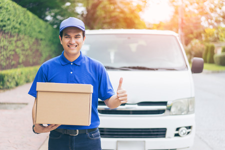Delivery concept - Smiling happy young asian handsome man  show thumbs up and postal delivery courier man in front of cargo van delivering package holding box with service mind and blue uniform Standard-Bild