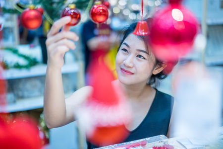 Portrait of smiling young Asian woman choosing gifts and decorations at Christmas fair and new year at department store. 스톡 콘텐츠