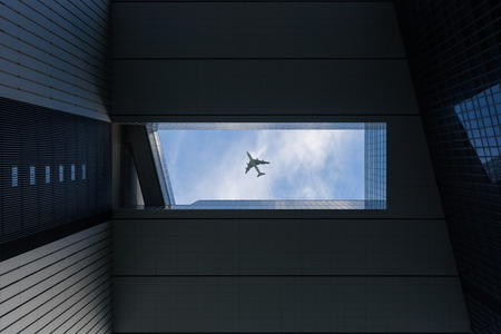 Airplane flying over building at Central Business District in Hong Kong. Hongkong city Фото со стока