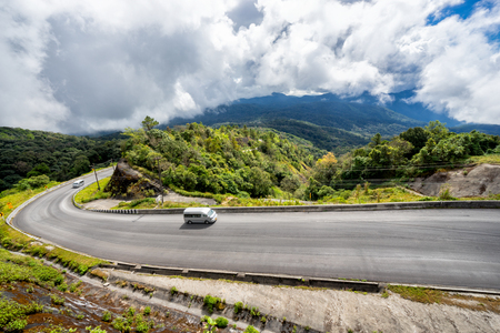 Morning scence of car driving to the top with curve of road at Doi Inthanon National park in Chiang Mai Province, Thailand.