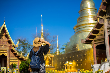 Young woman traveler traveling to Wat Phra Singh temple. This temple contains supreme examples of Lanna art in the old city center of Chiang Mai,Thailand.