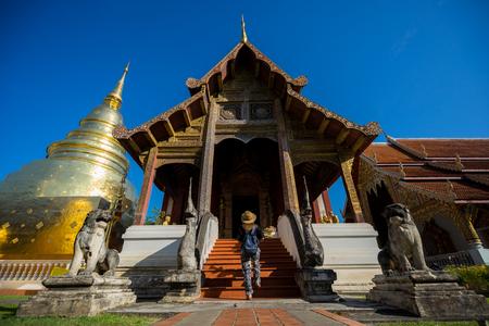와트 Phra Singh 사원 여행 젊은 여자 여행자. 이 성전은 태국 치앙마이의 구시 가지에있는 란나 예술의 훌륭한 예를 담고 있습니다.