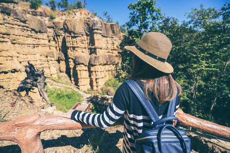 Young asian woman traveler travelling to wonderful soil cliff Pha Cho at Mae Wang National Park, Doi Lo district, Chiang Mai, Thailand.