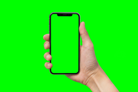 Man's hand shows mobile smartphone with green screen in vertical position isolated on green background Stock fotó - 90607767