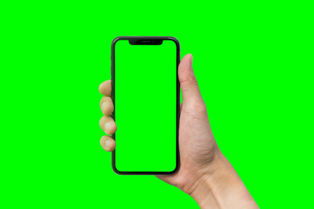 Mans hand shows mobile smartphone with green screen in vertical position isolated on green background 스톡 콘텐츠