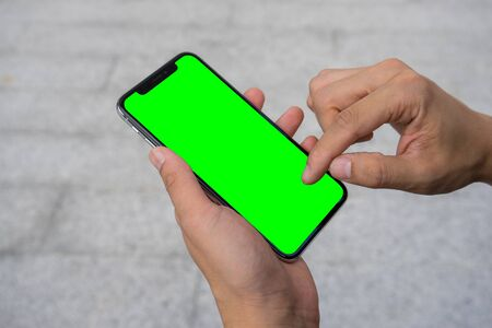 Mans hand using mobile smartphone with green screen 스톡 콘텐츠