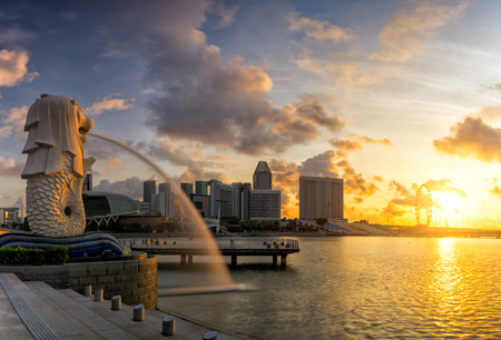 AUGUST 17, 2016 SINGAPORE : The Merlion is a traditional creature with a lion head and a body of a fish, seen as a symbol of Singapore.Landscape of the Singapore landmark financial district at sunrise 新聞圖片