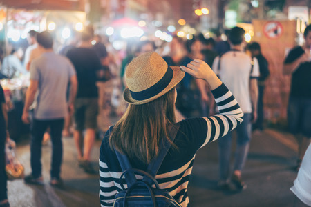 Young asian woman traveler backpacker with hat and bag traveling to Chiang Mai night walk street market at Chiang Mai Province, Thailand. 스톡 콘텐츠