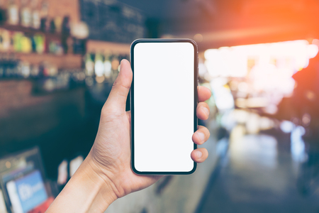 Mans hand shows mobile smartphone with white screen in vertical position, Blurred or Defocus image of Coffee Shop or Cafeteria for use as Background vintage tone. - mockup template and clipping path Stock Photo