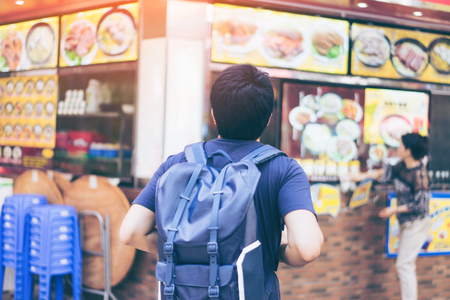 Young man traveler is visiting at Mongkok in Hong Kong for find some restaurant for eat noodles.
