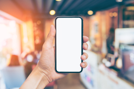 Mans hand shows mobile smartphone with white screen in vertical position, Blurred or Defocus image of Coffee Shop or Cafeteria for use as Background vintage tone. - mockup template and clipping path 스톡 콘텐츠
