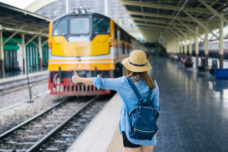 Young woman traveler with sky blue backpack and hat looking the map with train background at train station Bangkok. Traveling in Bangkok Thailand. Travel concept 스톡 콘텐츠