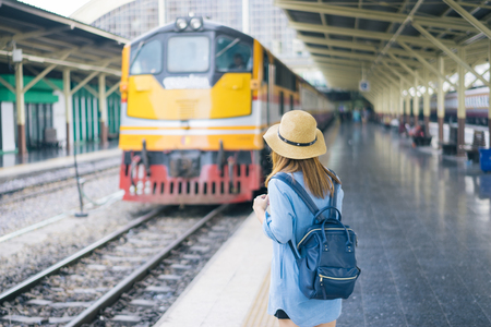 Young woman traveler with sky blue backpack and hat looking the map with train background at train station Bangkok. Traveling in Bangkok Thailand. Travel concept 版權商用圖片