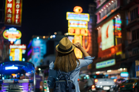 Young asian woman traveler with blue backpack and hipster hat looking night view on road with tuk tuk Thailand background at China Town Bangkok. Traveling in Bangkok Thailand 스톡 콘텐츠