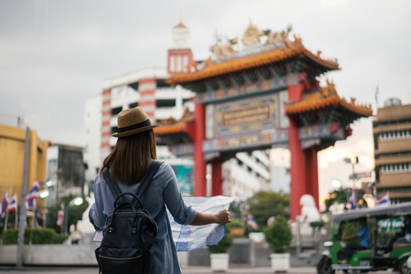 Young asian woman traveler with blue backpack and hipster hat looking map with tuk tuk Thailand background at China Town Bangkok. Traveling in Bangkok Thailand Standard-Bild