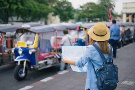 Young woman traveler with sky blue backpack and hat looking the map with tuk tuk Thailand background from china town Bangkok. Traveling in Bangkok Thailand. Travel concept