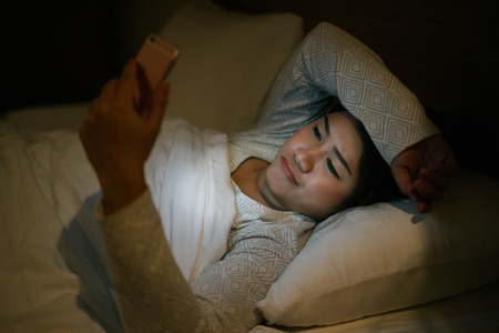 Young asian woman on bed late at night texting using mobile phone sleepy and tired in internet communication overuse and smartphone addiction. Wife using smartphone waiting husband with boring emotion