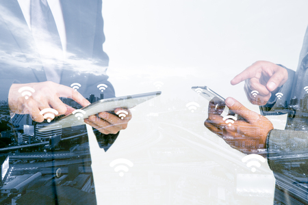 Double Exposure of a businessman use smartphone on Blue tone city scape and network connection concept , Wifi Wireless business district background.