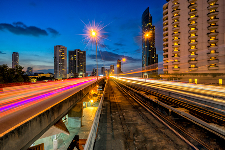 Sunset scence of Bangkok Panorama skyline ,Aerial view of Bangkok modern office buildings and condominium in Bangkok city downtown with ligt trail of car on road at Bangkok , Thailand. And skytrain Stock Photo