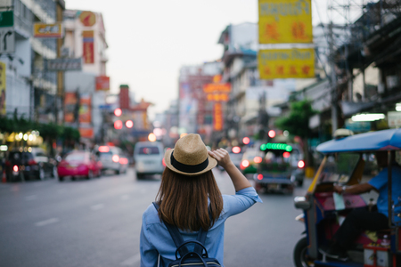 Young asian woman traveler with blue backpack and hipster hat looking night view on road with tuk tuk Thailand background at China Town Bangkok. Traveling in Bangkok Thailand Stock Photo