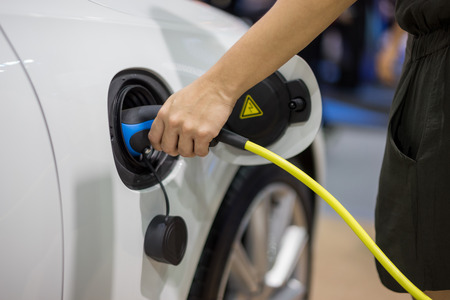 Hand holding Electric car charger. Power supply electric car charging for electric car technology transportation in the future. Stock Photo