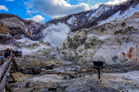 Traveler walking into Jigokudani, known in English as Hell Valley is the source of hot springs for many local Onsen Spas in Noboribetsu, Hokkaido, Japan in winter Stock Photo