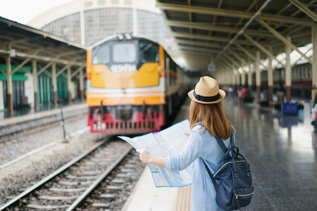 Young woman traveler with sky blue backpack and hat looking the map with train background at train station Bangkok. Traveling in Bangkok Thailand. Travel concept Stock Photo
