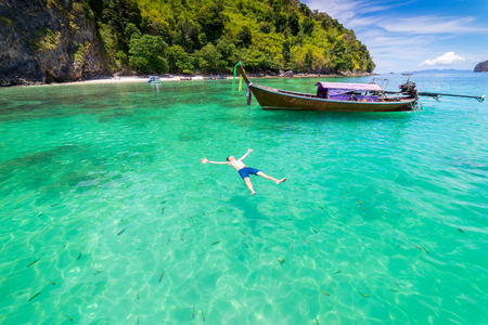 Young man traveler swimming surrounded by fish with long thai boat in Krabi Sea at Andaman Sea, Thailand
