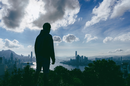 Silhouette of young man traveler is visiting at Braemar hill Hong Kong viewpoint in Hong Kong for looking scene of sunset. Stock Photo