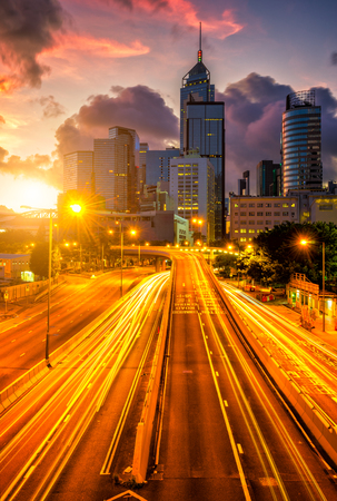 Traffic at central district in Hong Kong at sunrise time. Car light trails and urban cityscape in Hongkong city . Stock Photo