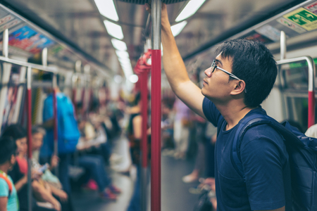 Young man traveler is visiting at Hongkong by subway MTR train. The Mass Transit Railway is the rapid transit railway system in Hong Kong. Stock Photo