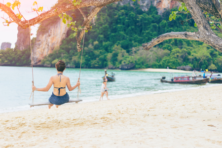 Young asian woman traveler in bikini relaxing and enjoying on wooden swing under tree and looking destinations beach, Pak Bea island, Andaman sea, Krabi Province near Phuket Thailand.