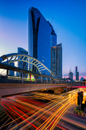 Panorama of Chong Nonsi, Sathorn Business district at Bangkok BTS sky train station public sky walk bridge with the modern office buildings with light trails background at sunset at Bangkok Thailand. Stock Photo