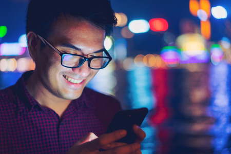 Young asian business handsome  smiling while reading his smartphone. Portrait of asian business man reading message with smart phone in outdoor with Hong Kong business district background