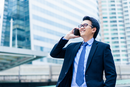 Closeup portrait of asian handsome business man using smartphone and smiling with happinest