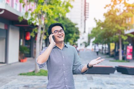 Young asian handsome businessman smilling and using his smartphone. Portrait of asian business man happy and using smart phone in outdoor.