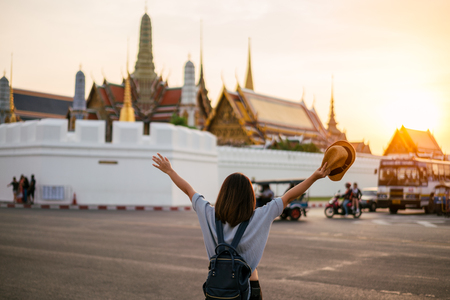 Young woman traveler travelling into Grand palace and Wat Phra Kaew at sunset Bangkok, Thailand. Amazing beautiful landmark of Bangkok Thailand. Temple of the Emerald Buddha.