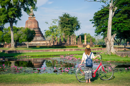 Young woman traveler travelling by bicycle into Wat Mahathat temple in the Sukhothai Historical Park contains the ruins of old Sukhothai, Thailand Stock Photo