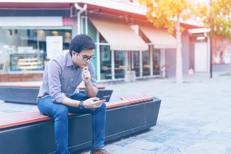 Young asian handsome businessman concentrated while reading his smartphone. Portrait of asian business man reading message with smart phone in outdoor. Standard-Bild