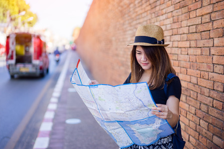 Young asian woman traveler with hat and bag looking map at Tha Pae Gate at the old Chiangmai city in Chang Mai, Thailand.