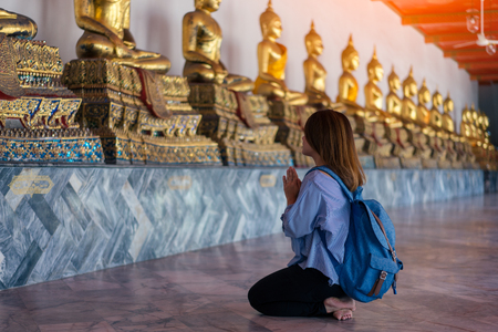Young woman traveler with backpack respecting or pray at many buddha statue in Wat Pho at Bangkok Thailand. Traveling in Bangkok Thailand