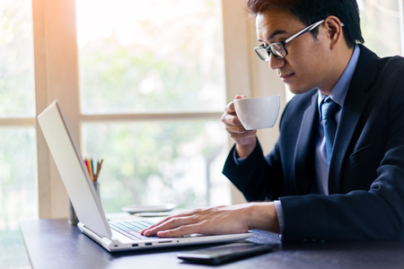 Young happy asian businessman using his laptop with a cup of coffee on office desk. Portrait of business man using laptop in office.