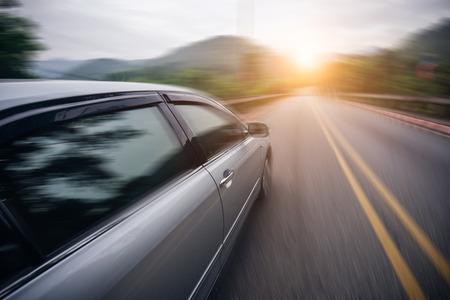 Car driving on asphalt road at sunset go to travel, motion blur