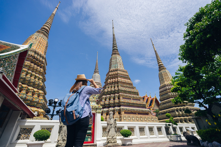 Young asian woman traveler with backpack and hat looking the architecture in Wat Pho at Bangkok Thailand. Traveling in Bangkok Thailand 스톡 콘텐츠