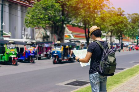 Young asian man traveler with sky blue backpack and hat looking map find the way with tuk tuk thailand background from wat pho at Bangkok Thailand