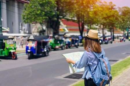 Young woman traveler with sky blue backpack and hat looking map find the way with tuk tuk thailand background from wat pho at Bangkok Thailand 스톡 콘텐츠
