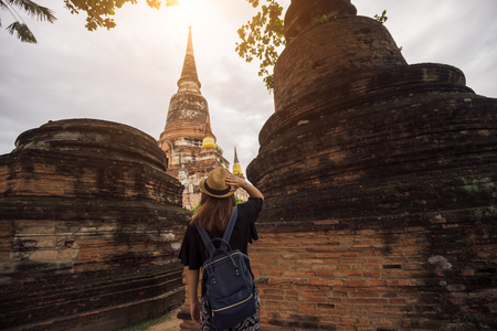 Young woman traveler with sky blue backpack and hat looking Wat Yai Chai Mongkol (or Mongkhon) temple background from Ayutthaya near Bangkok Thailand. Traveling in Ayutthaya near Bangkok Thailand 스톡 콘텐츠