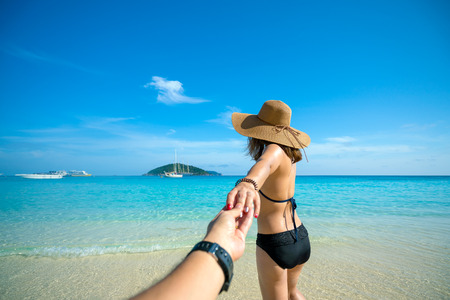 Romantic scene of young love couple in Similan islands in Andaman sea at phang nga near Krabi and Phuket in southern of Thailand. Hand man holding hand woman in black bikini and hat walking into a sea 스톡 콘텐츠
